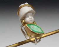 Sweet boy child with large, boat-shaped Colombian emerald. A lustrous green color and revealing gard..