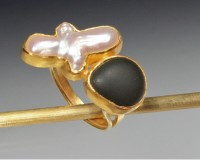 This is a large and dramatic ring that pairs two opposites.  A white lustrous pearl is set next to a..