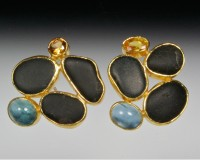 Small cluster of black basalts surrounded by mixed gemstones.  Shown here with citrines and aquamari..