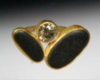 Giant cognac diamonds flanked by two basalt beachstones set in 22K gold...