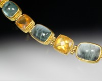 Cool blue aquamarine cabochons with vibrant orange fire opals from Mexico.  22K gold bezels and 14K ..