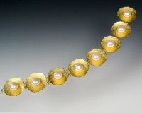 Luscious pearls set in luminous 22K gold concave textured discs.  Secure clasp with 14K gold hinges ..