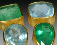 Opposite earrings with emerald and aquamarine.  Brilliant hues and dynamic stones in 22K gold bezels..