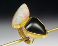 Lustrous black basalt is set in contrast to luminous Australian opal.  Set in 22K gold bezel with 14..